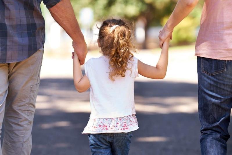 Una bambina ripresa da dietro con i genitori