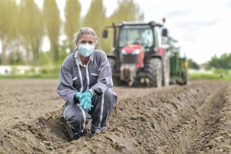 Una giovane imprenditrice del settore agricolo davanti il suo trattore
