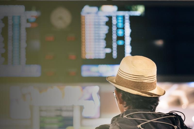Uomo che osserva un tabellone degli orari all'interno di una stazione