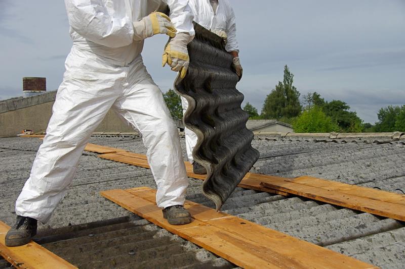 Operio che sta operando la rimozione di una lastra di cemento-amianto