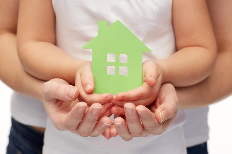 Due mani di adulto che sostengono due mani di bambino, con in mano la sagoma di cartone di una casa