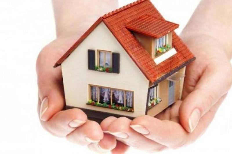 Mani sostengono il modellino di una casa