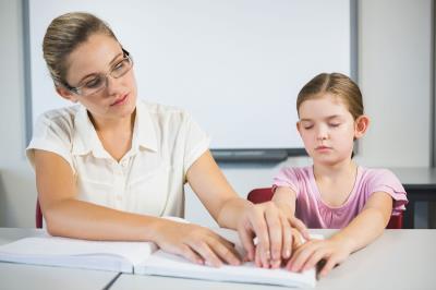 Docente che aiuta un'alunna con disabilità visiva